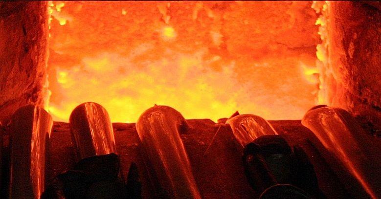 Glasstangen werden in der Glut des Ofenfeuers für die Verarbeitung erhitzt.