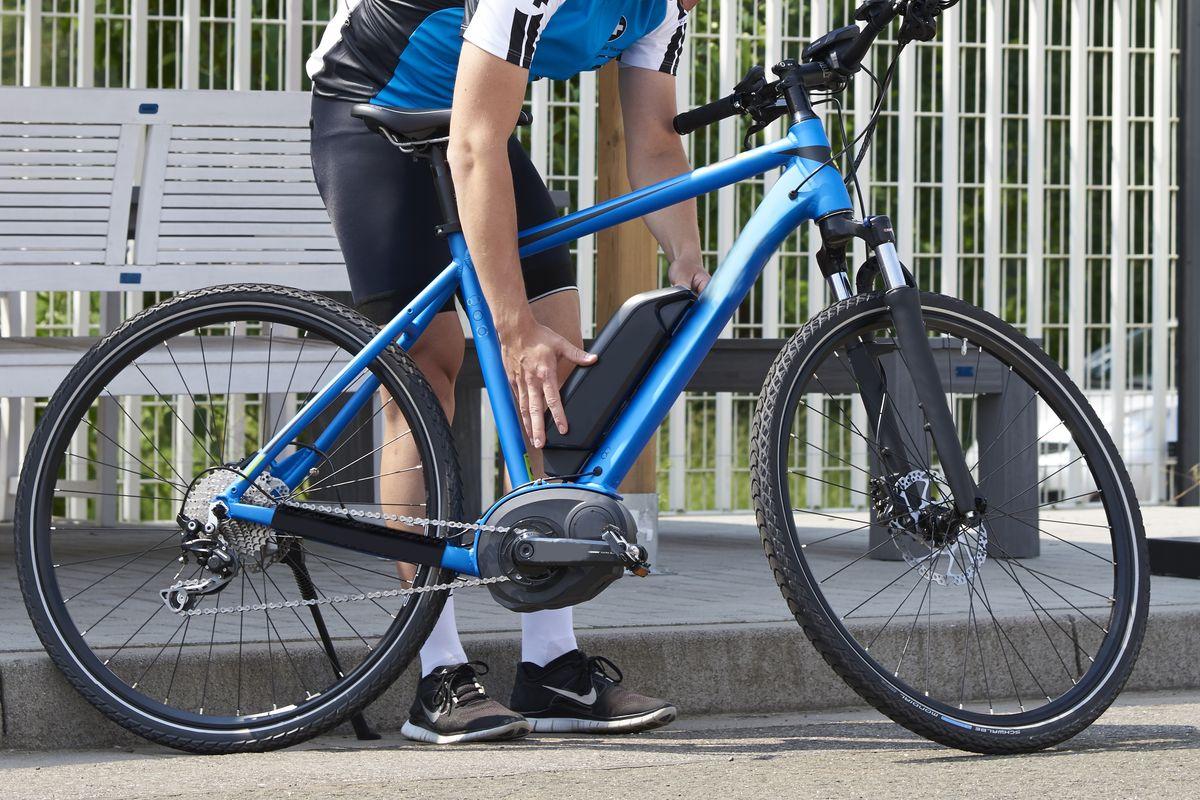 Mann wechselt Akku bei einem E-Mountainbike